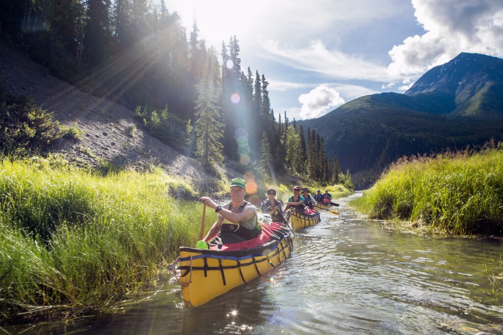 Group kayaks in Nahanni River in Canada