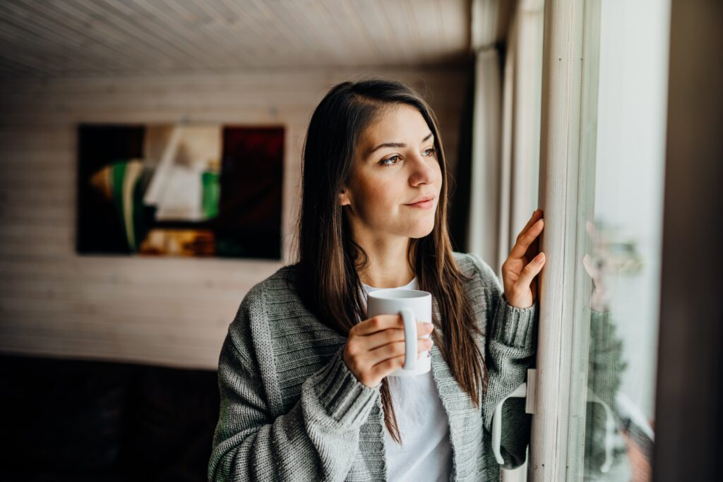Woman in quarantine looking outside the window