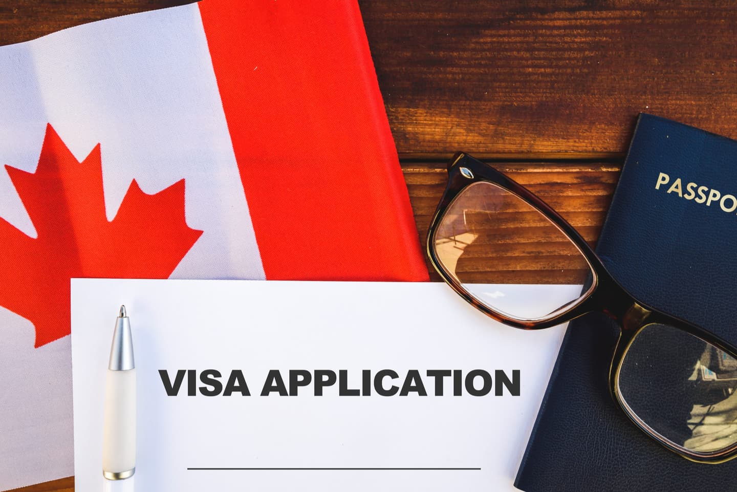 Visa application with Canadian flag and passport in background
