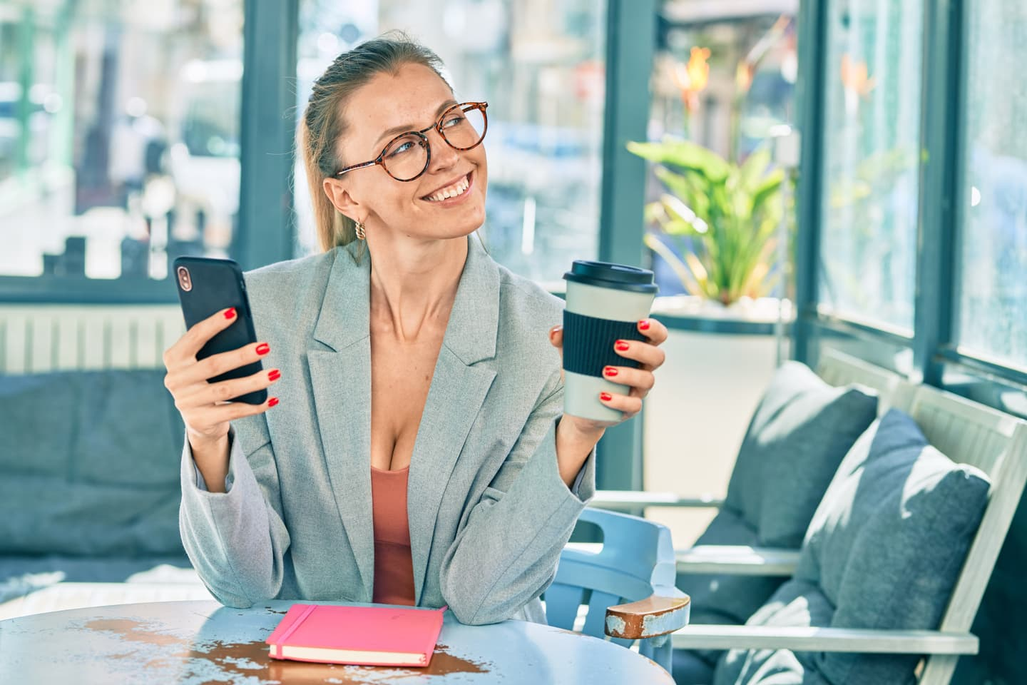 Woman smiling while holding her phone and coffee