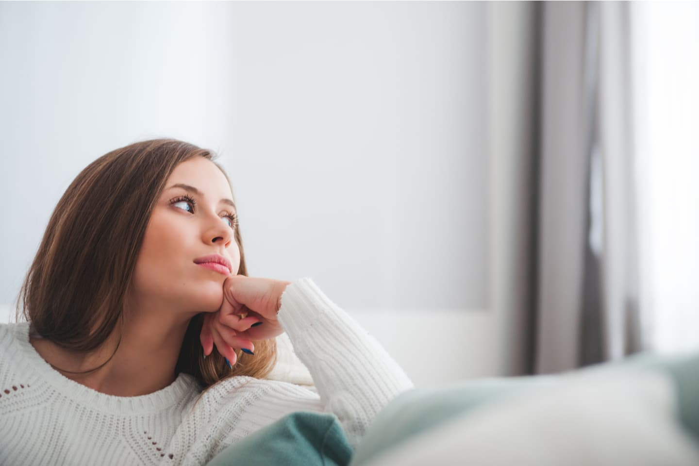 Young woman thinking on her couch