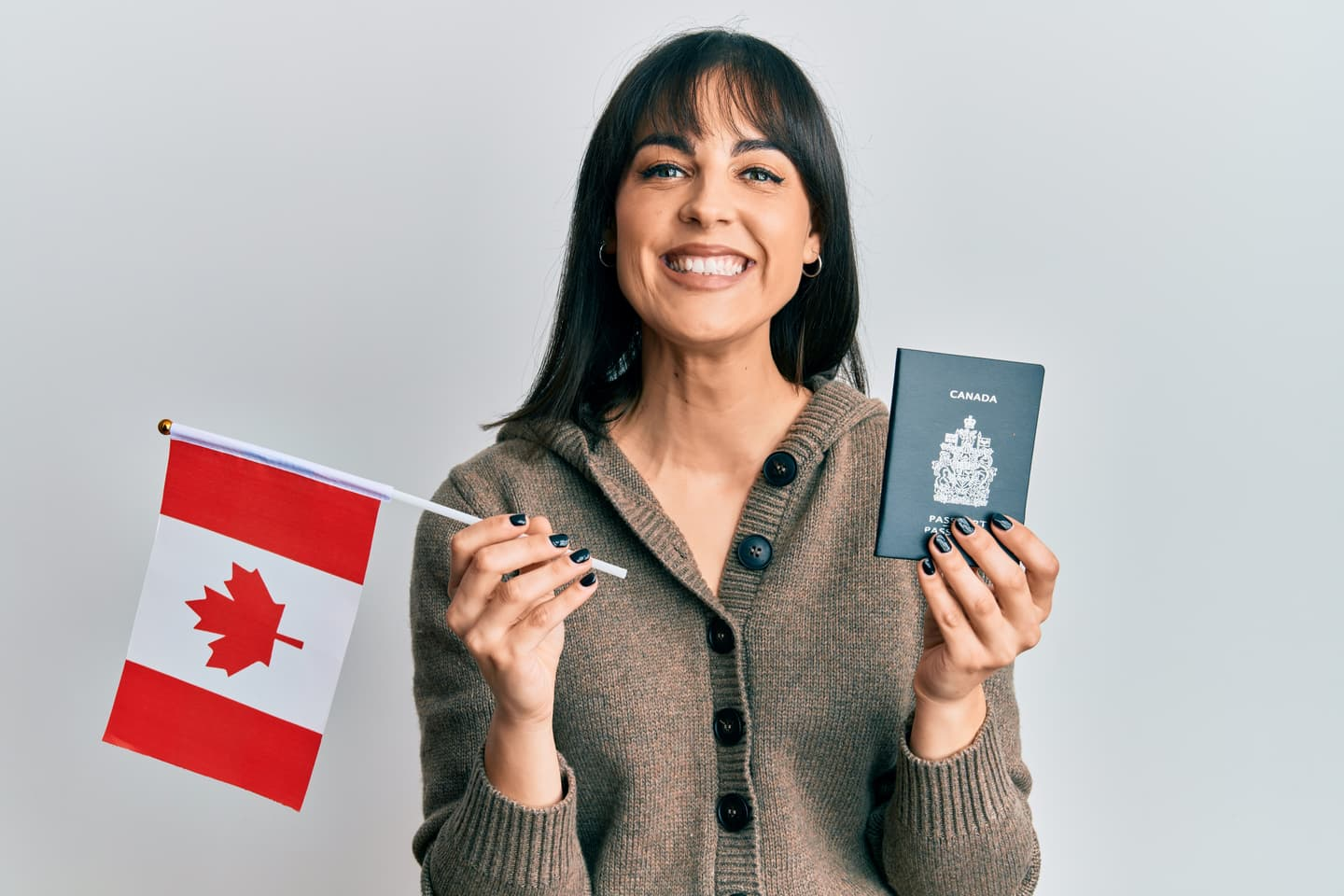 Woman holding Canadian flag and passport